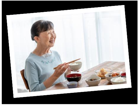 食事をしながら微笑む高齢女性